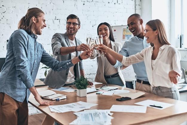 В нашу команду! группа молодых деловых людей, поджаривающих друг друга и улыбаясь, стоя в зале заседаний
