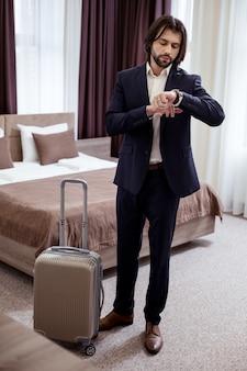 В аэропорт. серьезный хороший бизнесмен, проверяющий время, собираясь в аэропорт