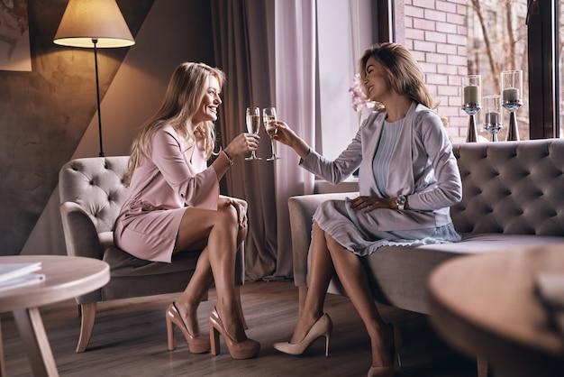 Нам! привлекательные молодые женщины жарят друг друга и улыбаются, проводя время в современной квартире
