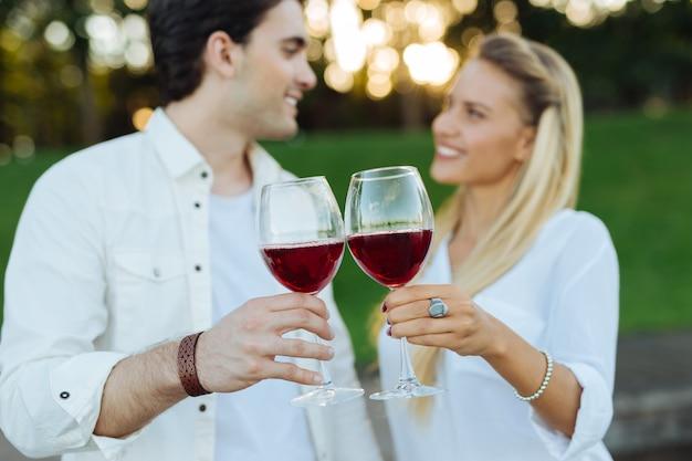 私たちに。うれしそうな幸せなカップルによって一緒にワインがチリンと鳴る2つのグラスの選択的な焦点