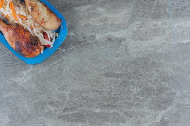 木の板にザワークラウトを添えてグリルした鶏の脚を見る。