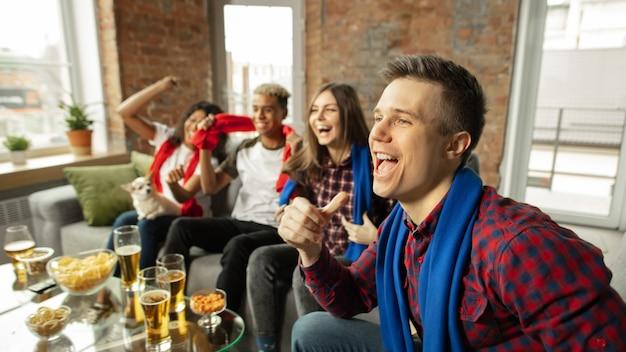К победе. взволнованные люди смотрят спортивный матч, чемпионат дома. многонациональная группа друзей.
