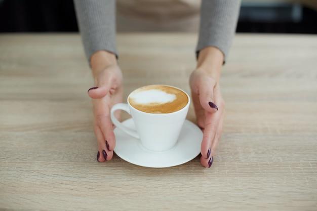 コーヒーショップのエプロンのバリスタは、顧客にtoれたての新鮮なコーヒーを与える