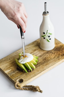 Toast, avacado sandwich and poached egg on a wooden chopping board.