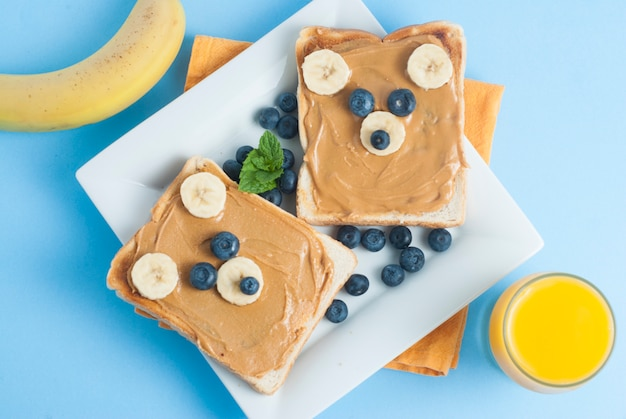 Toast bear shaped, peanut butter, banana, blueberry. funny food for kids.