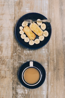 Toast bread and banana slices on plate with coffee cup on wooden table
