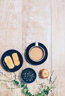 Toast bread; blueberries; apple and cup of coffee on wooden textured backdrop