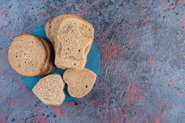Tostare le fette di pane in un piatto blu.