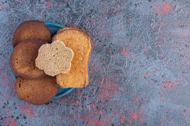 Поджарьте ломтики хлеба на синем блюде.