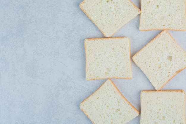 Ломтики хлеба тоста на мраморной предпосылке. фото высокого качества