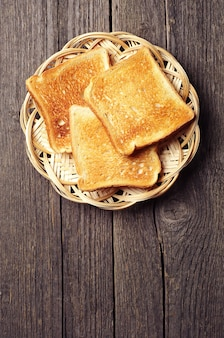 Toast bread in a wicker plate on vintage wooden background. with place for text.