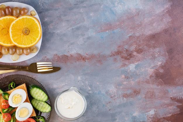 ゆで卵とフルーツプレートを大理石のテーブルに載せたトーストパン。