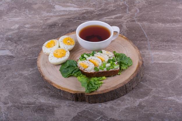 Pane tostato con uova sode ed erbe aromatiche servito con una tazza di tè. Foto Gratuite