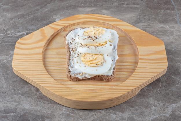 Pane tostato con uova sode sul piatto di legno.