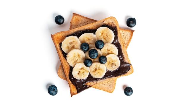 チョコスプレッド、ベリー、バナナを白で分離したトーストパン。