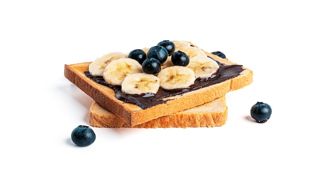 Хлеб тоста с шоколадным спредом, ягодами и бананом, изолированными на белом.