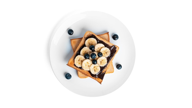 Toast bread with chocolate spread, berries and banana isolated on white. Premium Photo