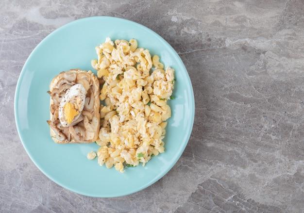 Pane tostato con uova e pasta sul piatto blu.