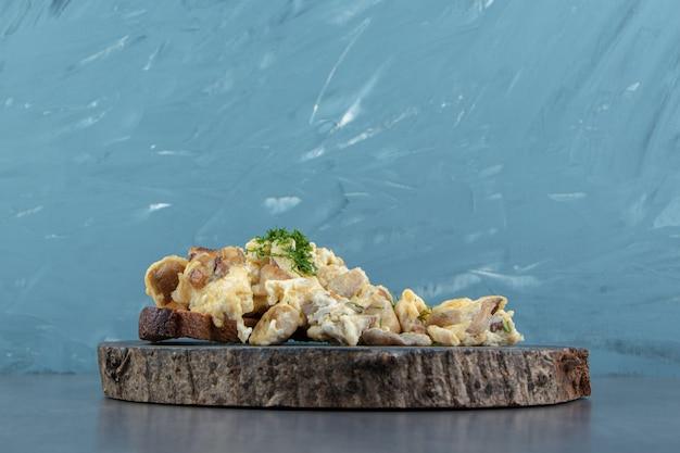 Pane tostato con insalata di uova su pezzo di legno.