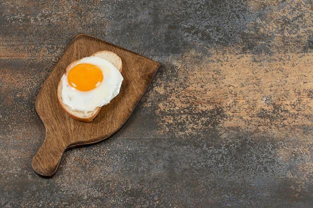 Pane tostato con uova su tavola di legno.