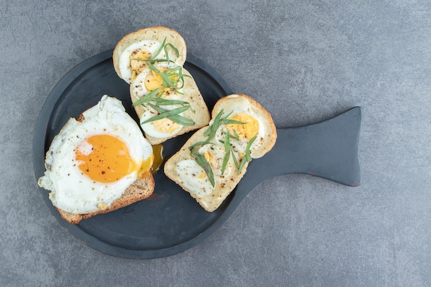 Toast bread with fried egg on black board.