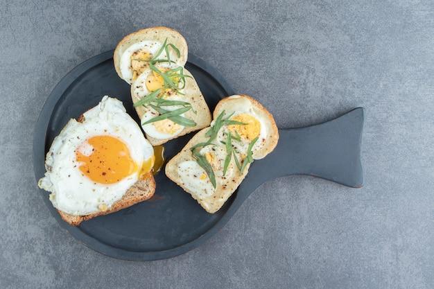Хлеб тоста с жареным яйцом на черной доске.