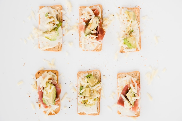 Toast bread with grated cheese; ham and avocado slice on white backdrop