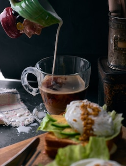 Тост хлеб с нарезанный авокадо, посыпать яйцом и зеленью на деревянной разделочной доске.