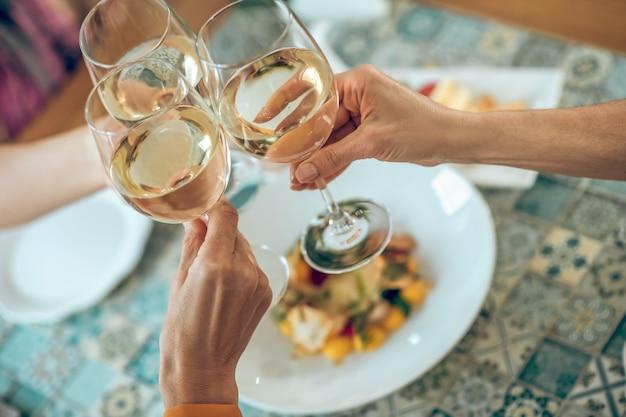 トースト。友人の手にワインとガルスの写真をクローズアップ