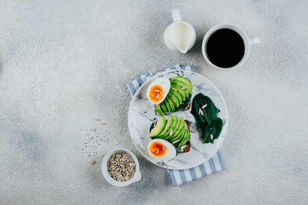 Toast on dark rye grain bread made with fresh sliced avocado, cream cheese, spinach and seeds
