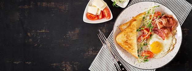 Toast, egg, bacon and tomatoes and microgreens salad