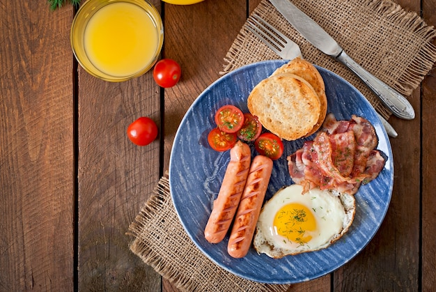 Toast, egg, bacon and vegetables in a rustic style on wooden surface