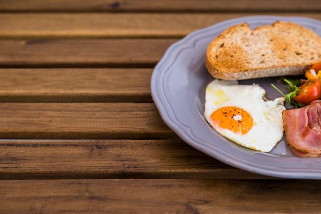 Тост; жаренное яйцо; бекон на керамической серой тарелке над деревянным столом