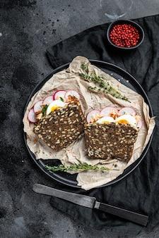 Тост из зернового хлеба с лососем горячего копчения, яйцом и редисом