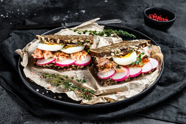 Toast from grain bread with hot smoked salmon, egg and radish. black background, top view.