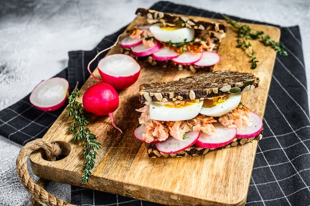 Toast from grain bread with hot smoked salmon, egg and radish. gray background, top view.