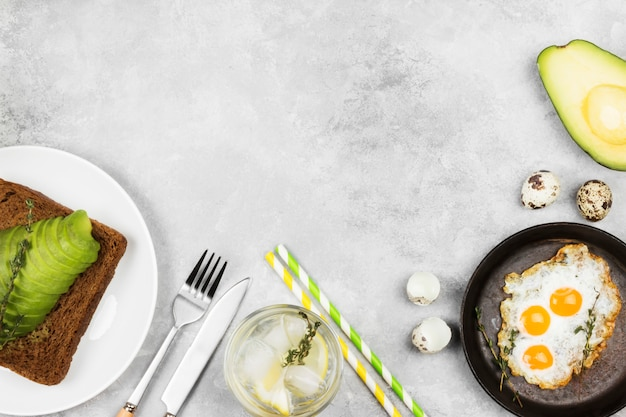 Toast from rye bread with avocado, fried eggs from quail eggs,  lemonade on a light background