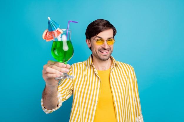 멋진 휴일을 건배하세요. 긍정적인 남자는 이국적인 바다 해변 리조트를 여행하는 것을 즐깁니다. 유리 녹색 칵테일은 파란색 배경 위에 격리된 흰색 노란색 옷을 입습니다.