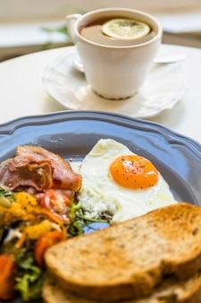 Toast; half fried egg; salad and bacon on gray plate in front of tea cup over the table
