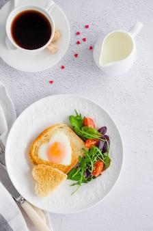 Тост в форме сердца с яйцом на белой тарелке с рукколой и помидорами черри
