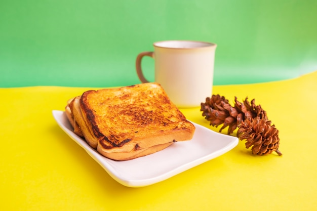 黄色と緑の紙の背景にトウヒの花と白いプレートと黒のコーヒーマグカップで乾杯。朝食のトースト。横の写真