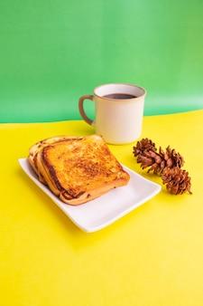 黄色と緑の紙の背景にトウヒの花と白いプレートと黒のコーヒーマグカップで乾杯。朝食のトースト。縦の写真