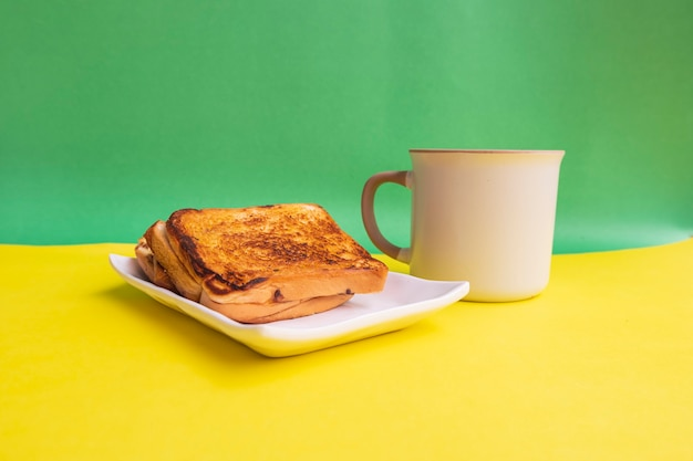 黄色と緑の紙の背景に白いプレートと黒のコーヒーマグカップで乾杯。朝食にトーストとブラックコーヒー。横の写真