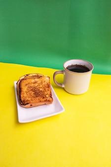 黄色と緑の紙の背景に白いプレートと黒のコーヒーマグカップで乾杯。朝食にトーストとブラックコーヒー。縦の写真