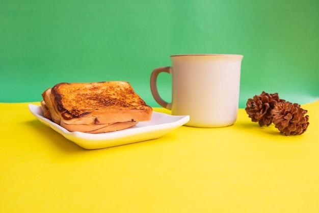 黄色と緑の紙の背景にトウヒの花の装飾と白いプレートと黒のコーヒーマグカップで乾杯。朝食にトーストとブラックコーヒー。横の写真