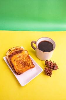 黄色と緑の紙の背景にトウヒの花の装飾と白いプレートと黒のコーヒーマグカップで乾杯。朝食にトーストとブラックコーヒー。縦の写真