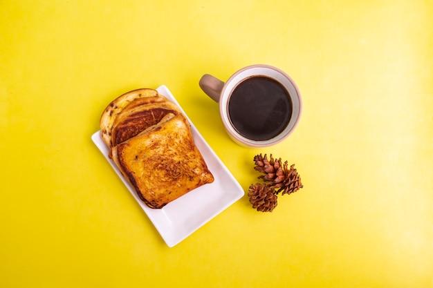 黄色い紙の背景にトウヒの花の装飾と白いプレートと黒のコーヒーマグカップで乾杯。朝食にトーストとブラックコーヒー。横の写真