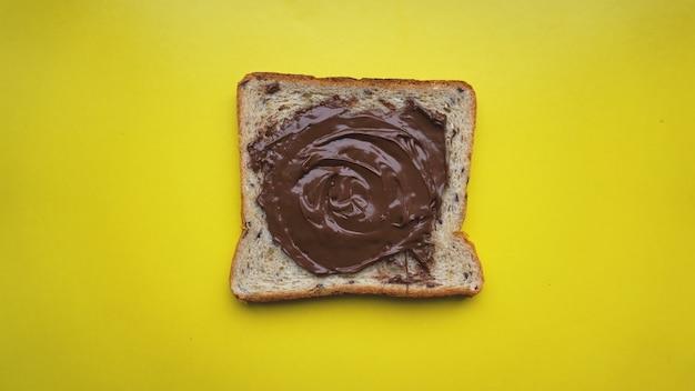 黄色の背景にトースト-チョコレートスプレッドでサンドイッチ。朝食の背景。上からの眺め-宇宙写真をコピーします。
