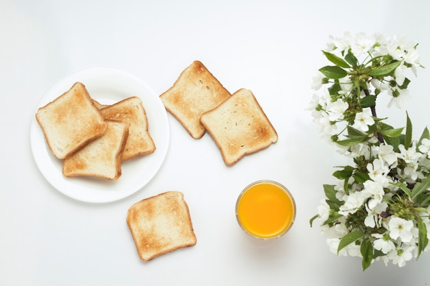 Toast, orange juice and blossoming cherry branches on a white