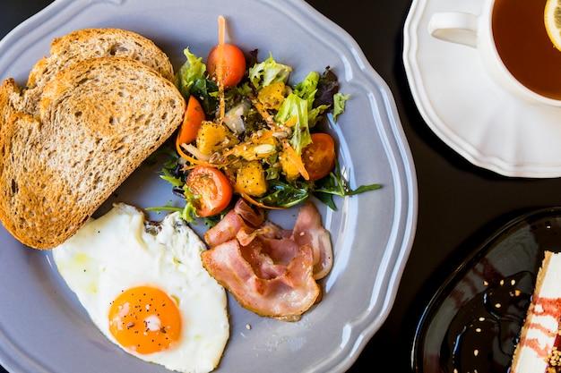 Toast; salad; fried eggs; bacon on ray plate